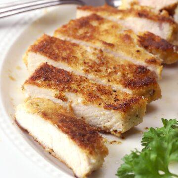 Pork chop sliced on a white plate.