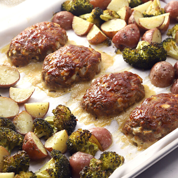 Sheet pan filled with mini meatloaves, potatoes, and broccoli.