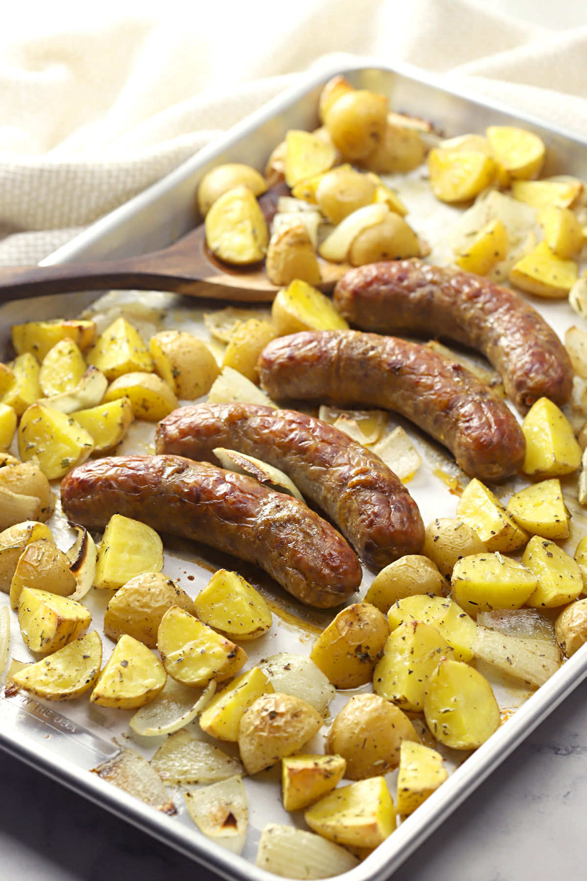 Sheet pan filled with italian sausage and potatoes.