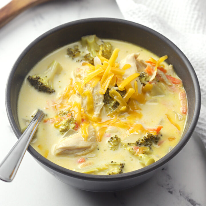 Bowl of chicken broccoli cheese soup with a spoon.