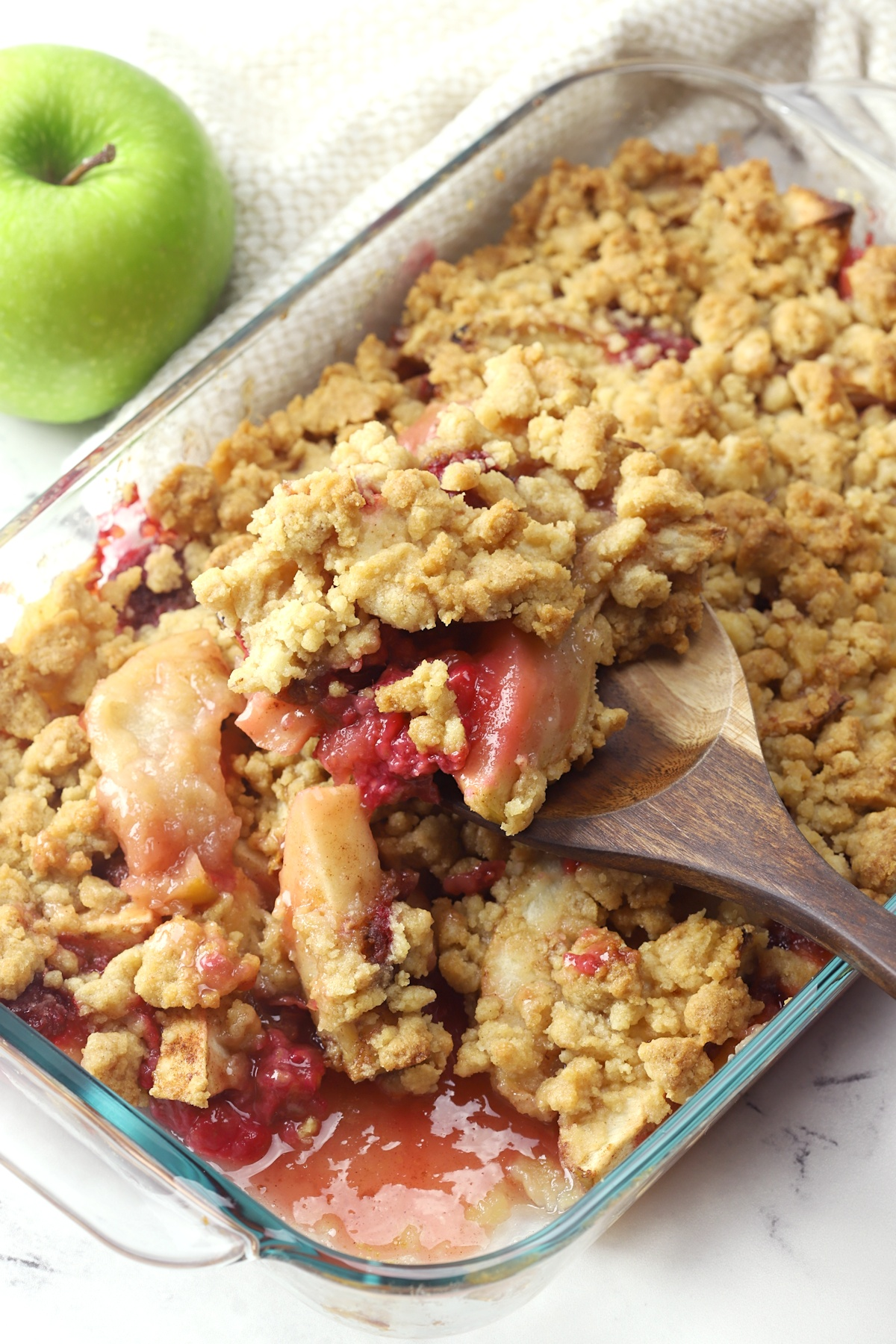 Wooden spoon scooping apple raspberry crumble from pan.