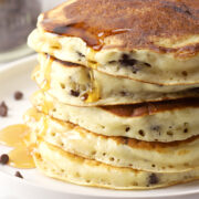 A stack of chocolate chip pancakes on a white plate.