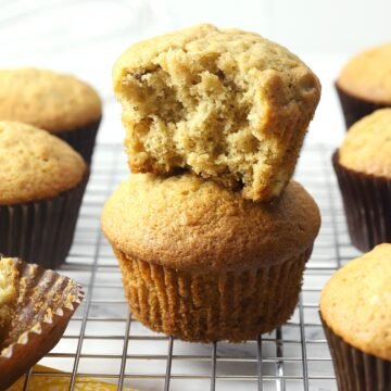 Banana nut muffins stacked on a cooling rack.