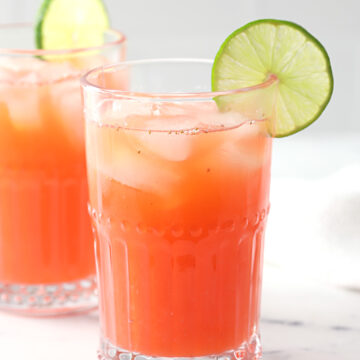 A glass of strawberry limeade garnished with a lime wedge.