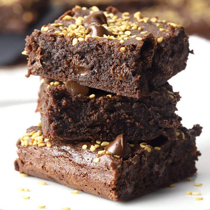 Stack of tahini brownies on a white plate.