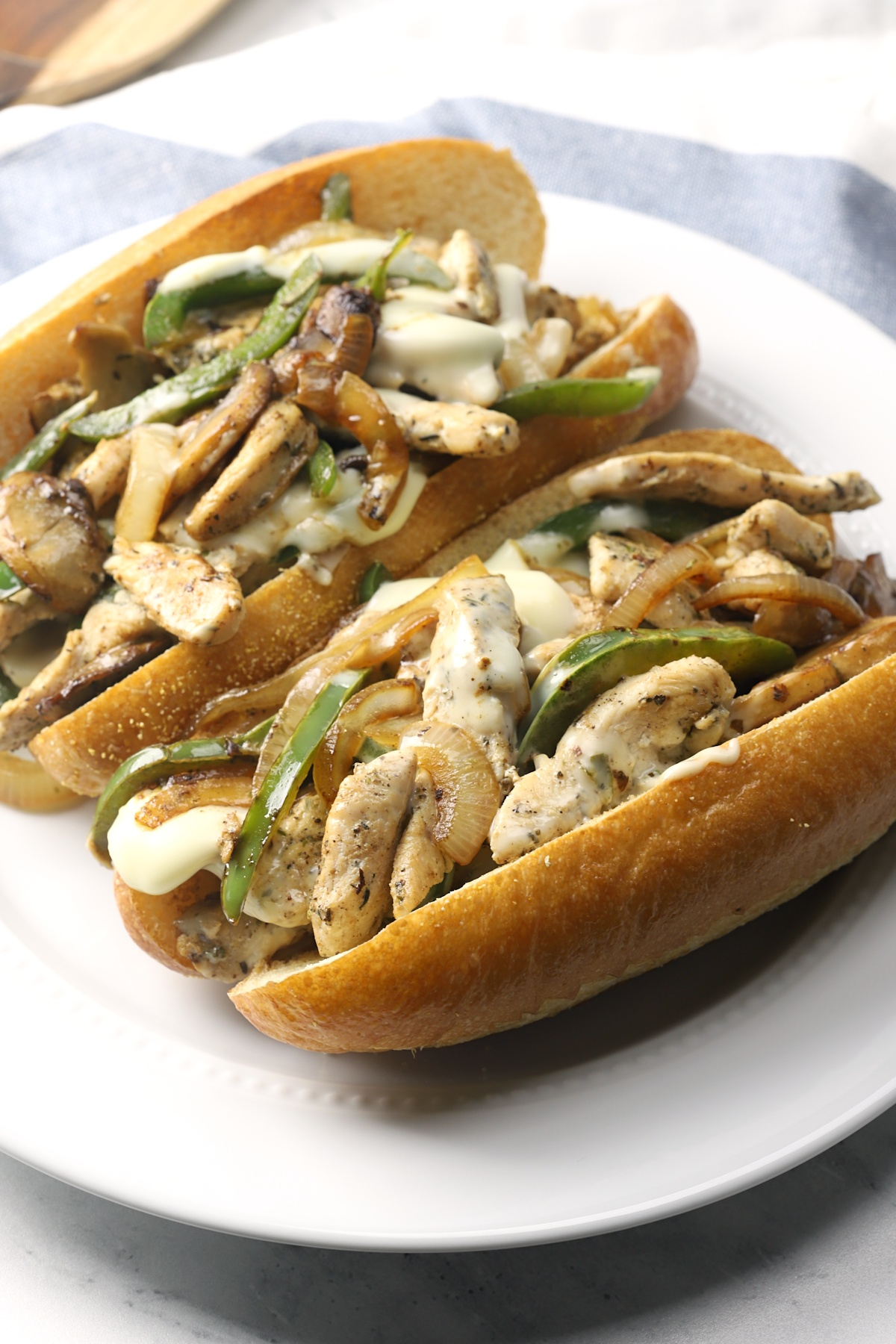 Two chicken cheesesteaks on a white plate.
