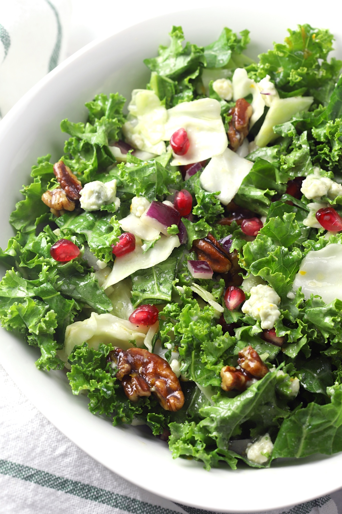 Kale and cabbage salad in a white bowl, topped with pomegranate arils and pecans.