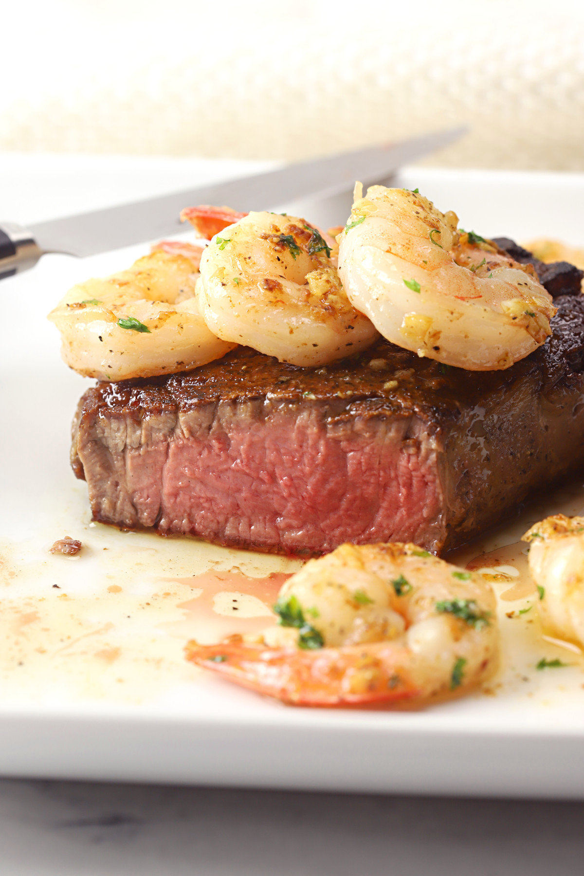 Filet mignon sliced in half and topped with garlic shrimp.