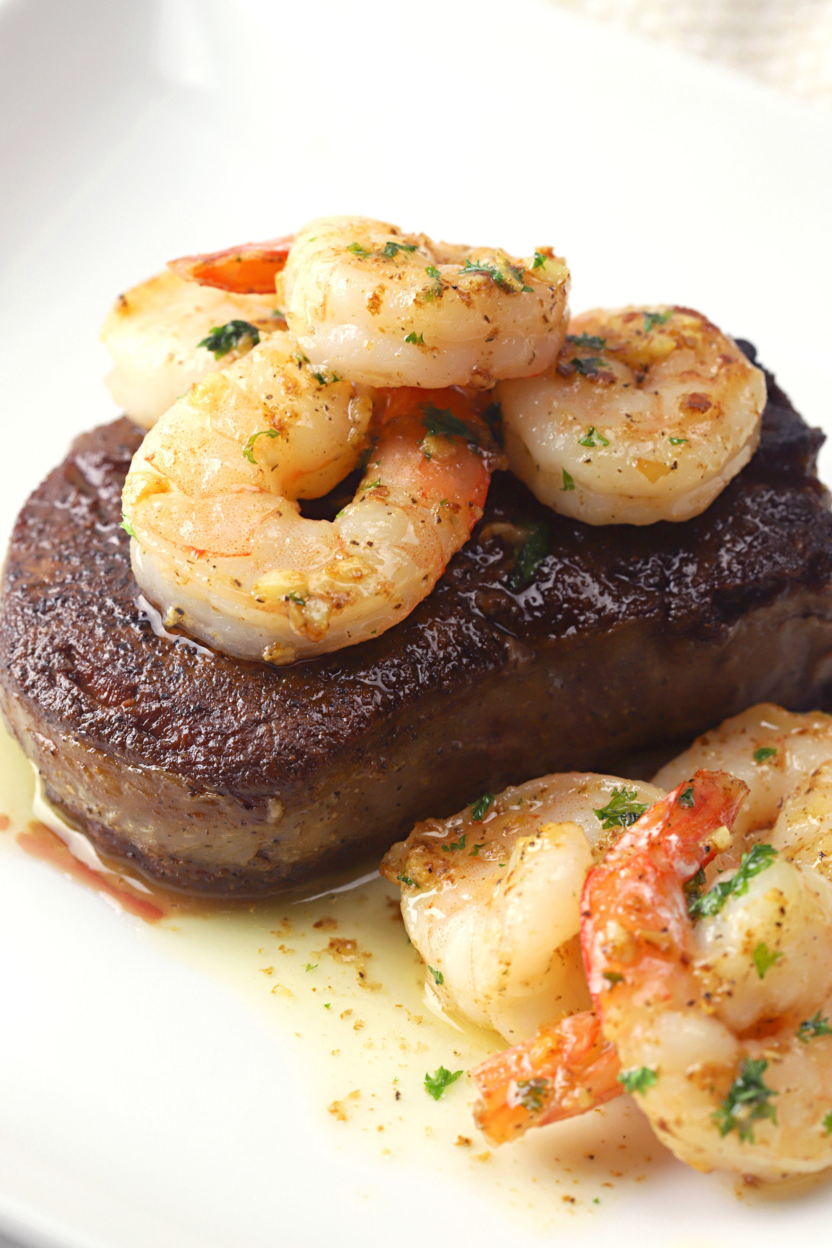 Filet mignon on a white plate, topped with shrimp.