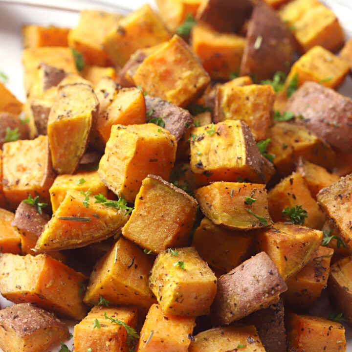 White plate filled with cubed roasted sweet potatoes.