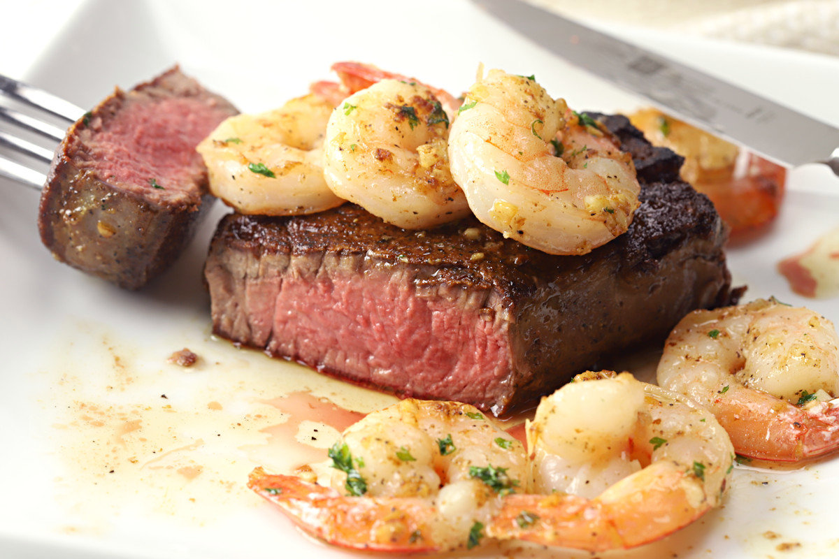Steak sliced in half, surrounded by and topped with shrimp.