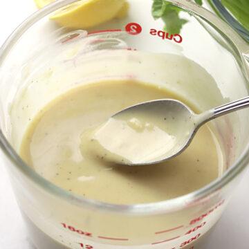Metal spoon in a bowl of salad dressing.