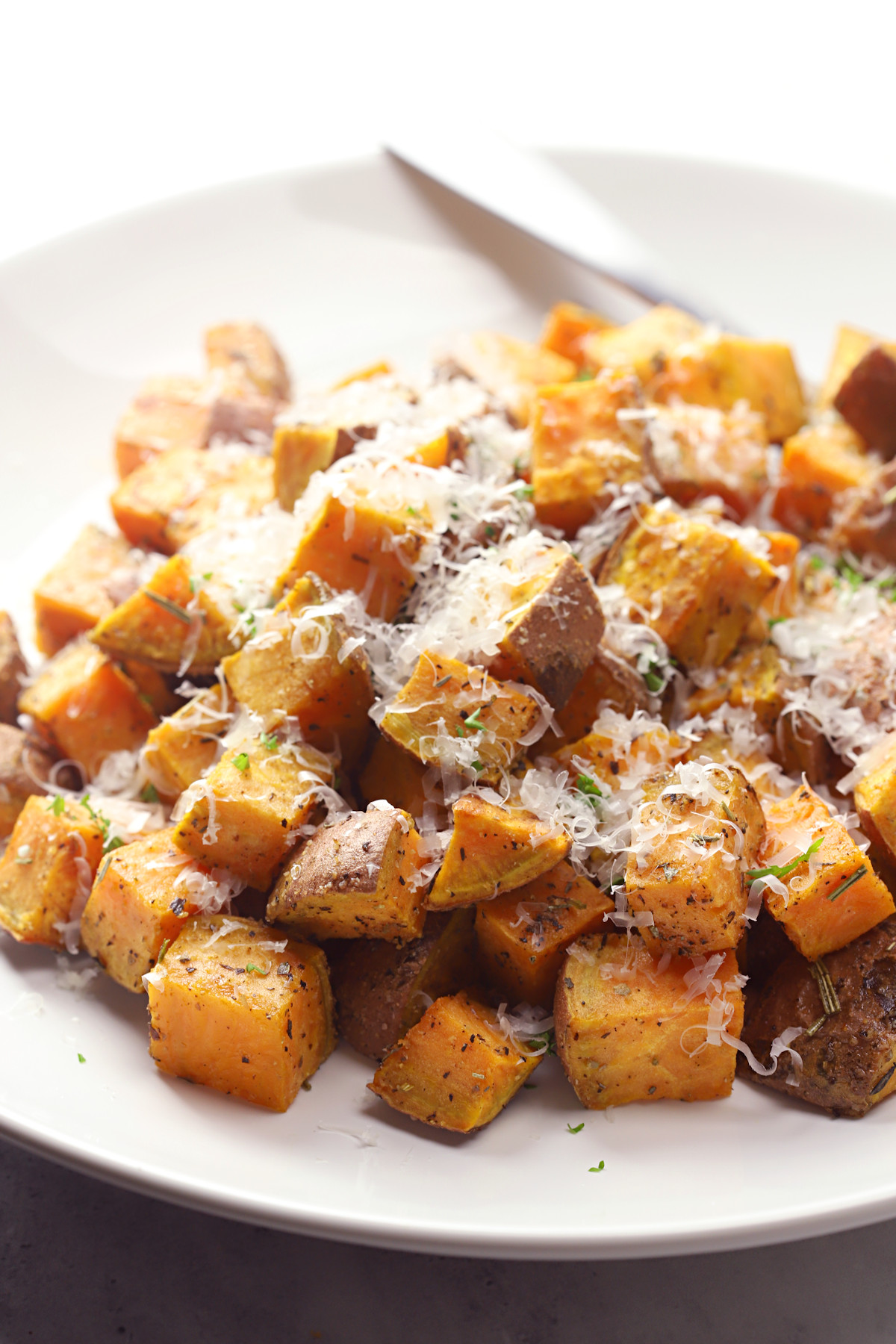 Sweet potatoes topped with grated parmesan cheese.