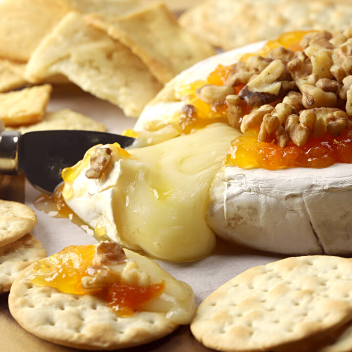 Melty wheel of baked brie on a wooden serving tray with crackers.