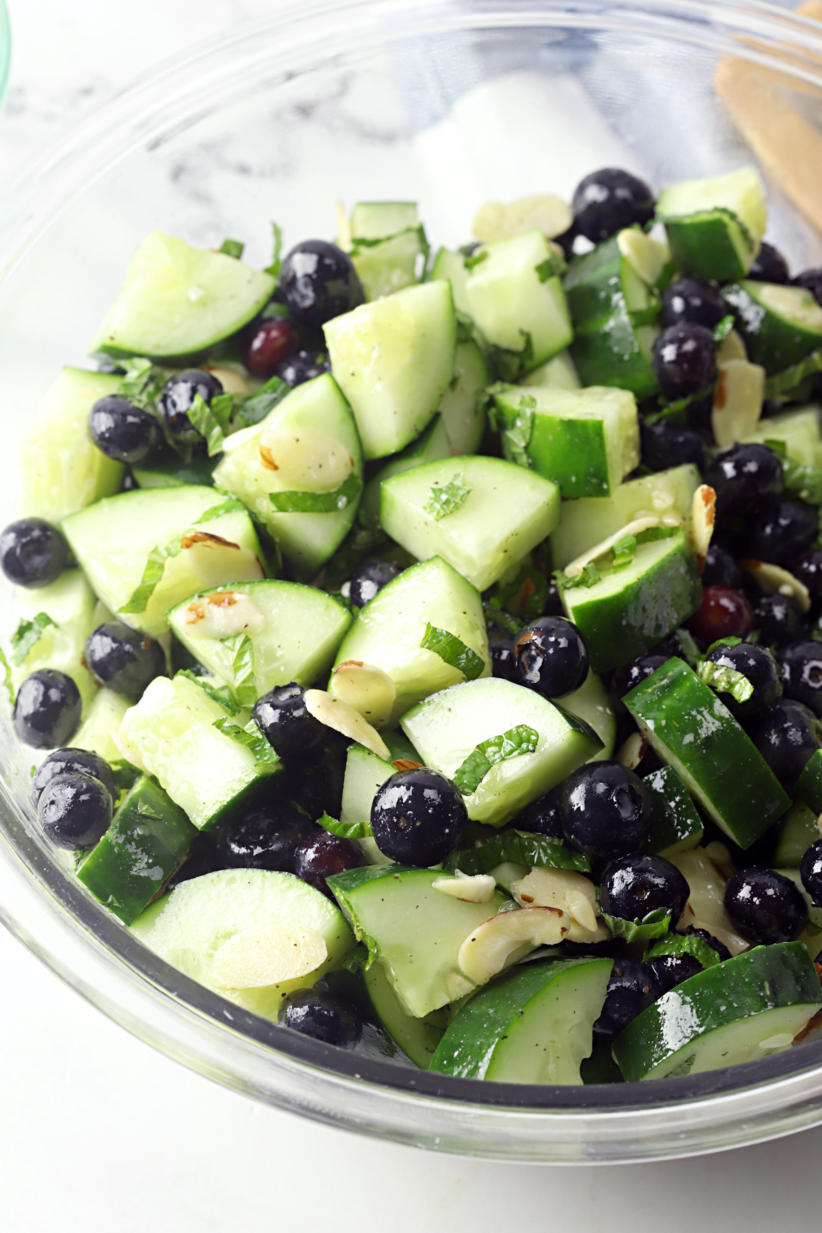 Glass bowl filled with cucumbers slices and blueberries.