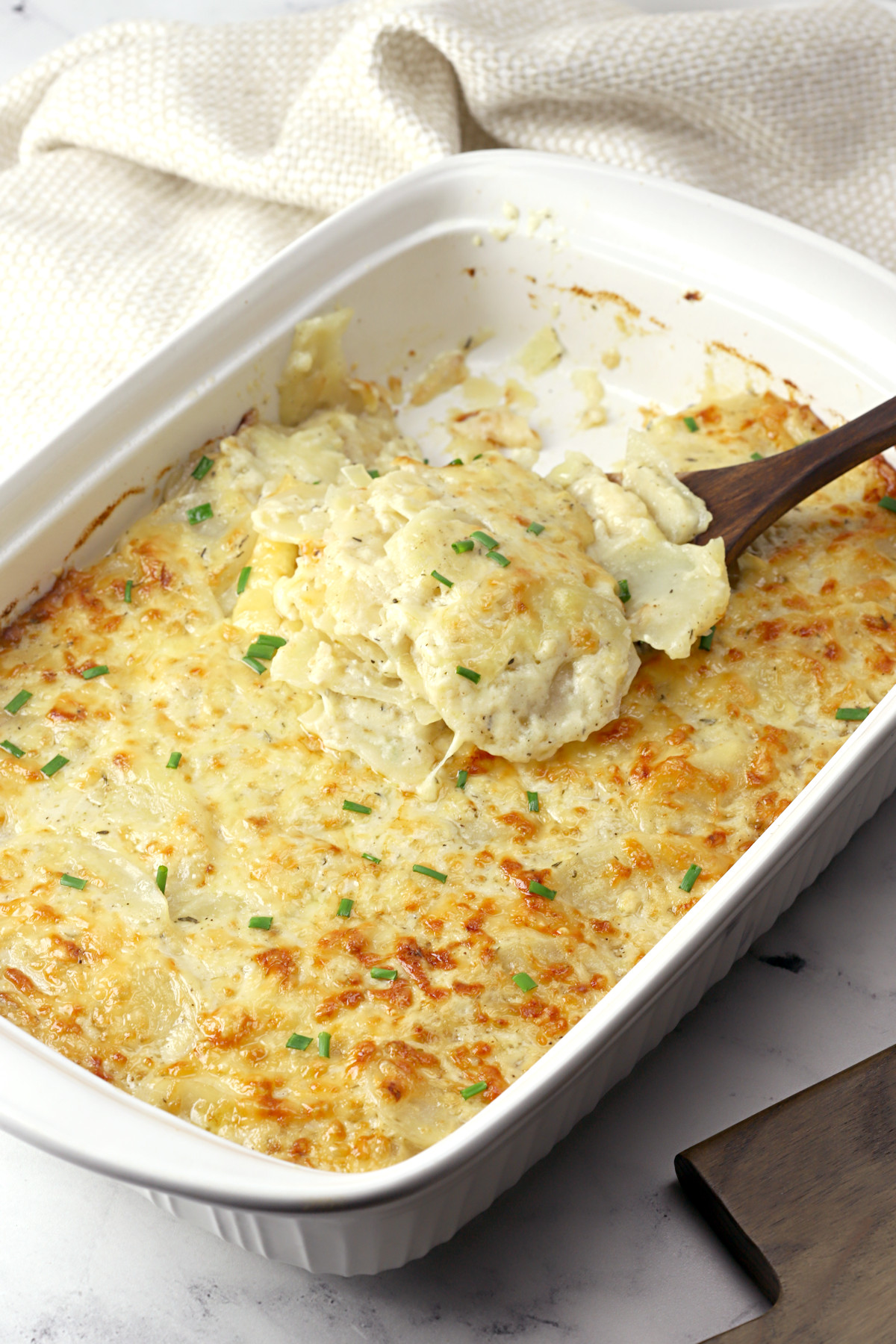 A white casserole dish filled with baked potatoes au gratin.