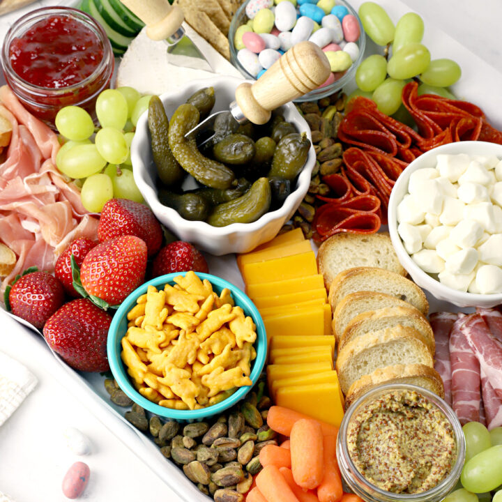 Meats, cheeses, crackers, and fruits set up on an Easter charcuterie board.