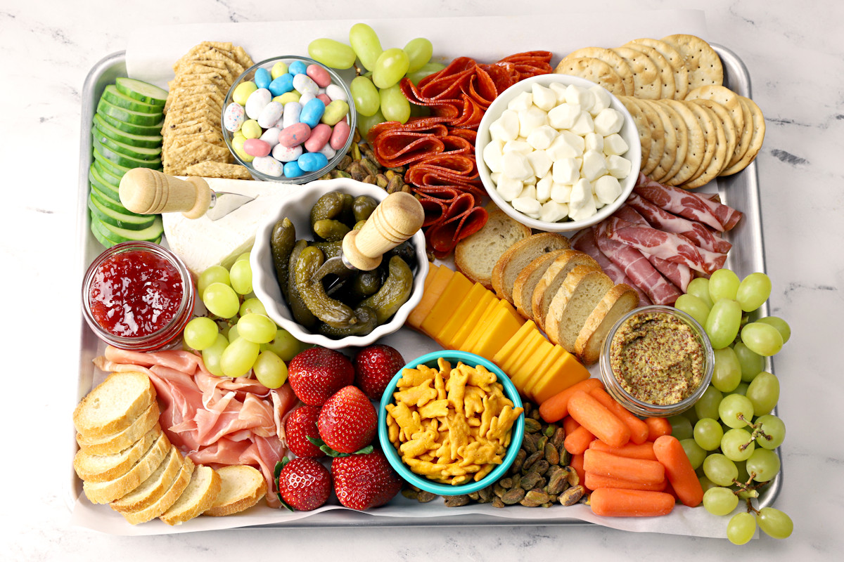 A half sheet pan filled with meats, cheeses, and crackers to make a charcuterie board.