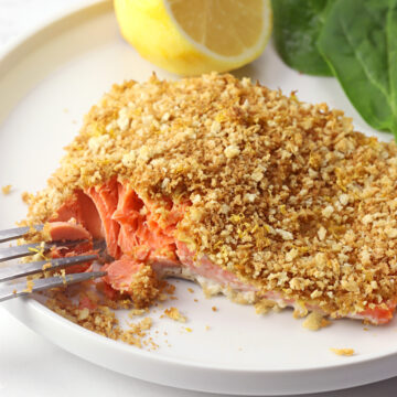 Flaking apart a piece of salmon with a metal fork.