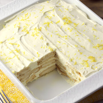 A slice taken from a lemon icebox cake in a white dish.