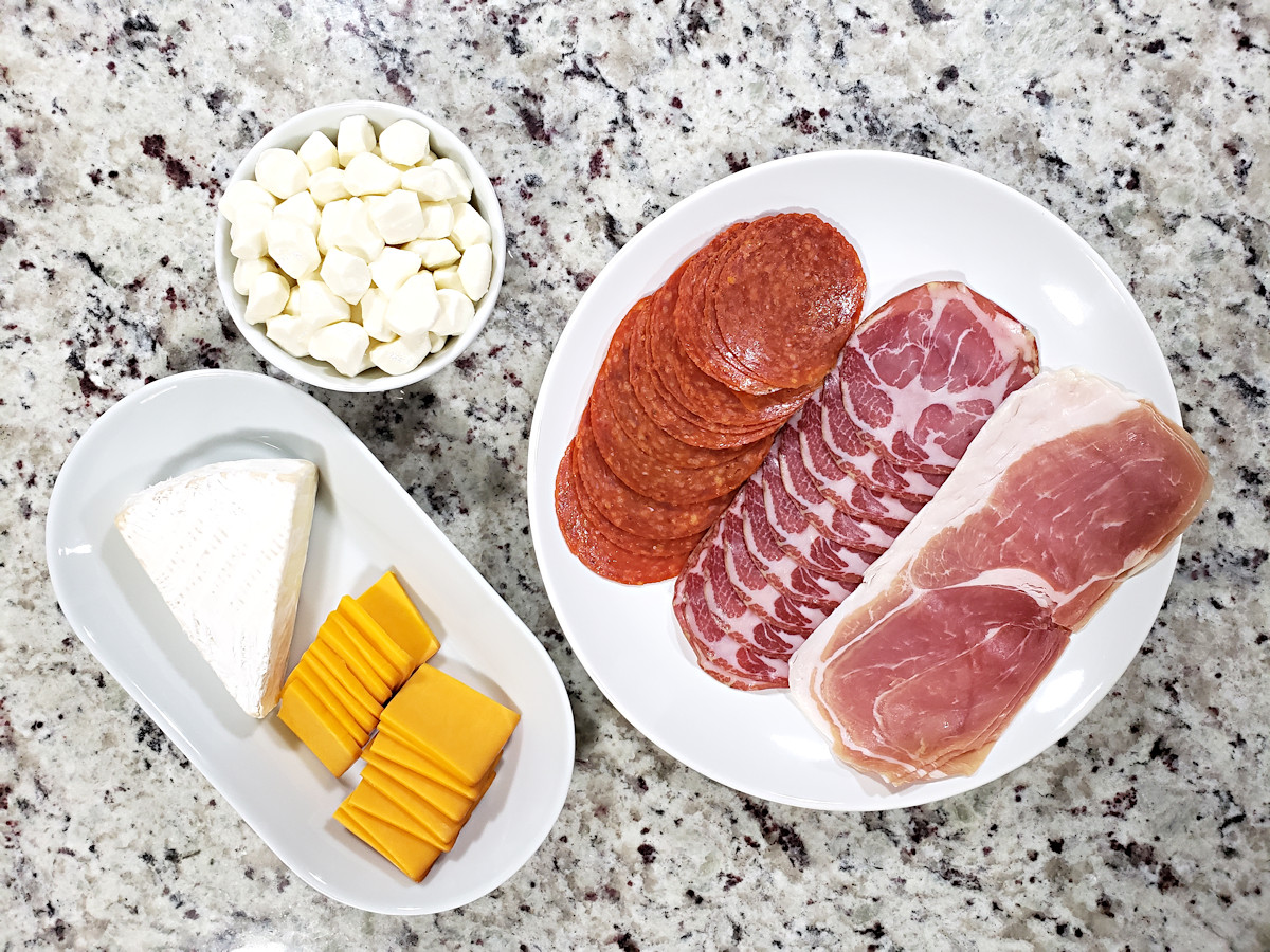 Cheeses and meats on white plates, ready to add to appetizer tray.