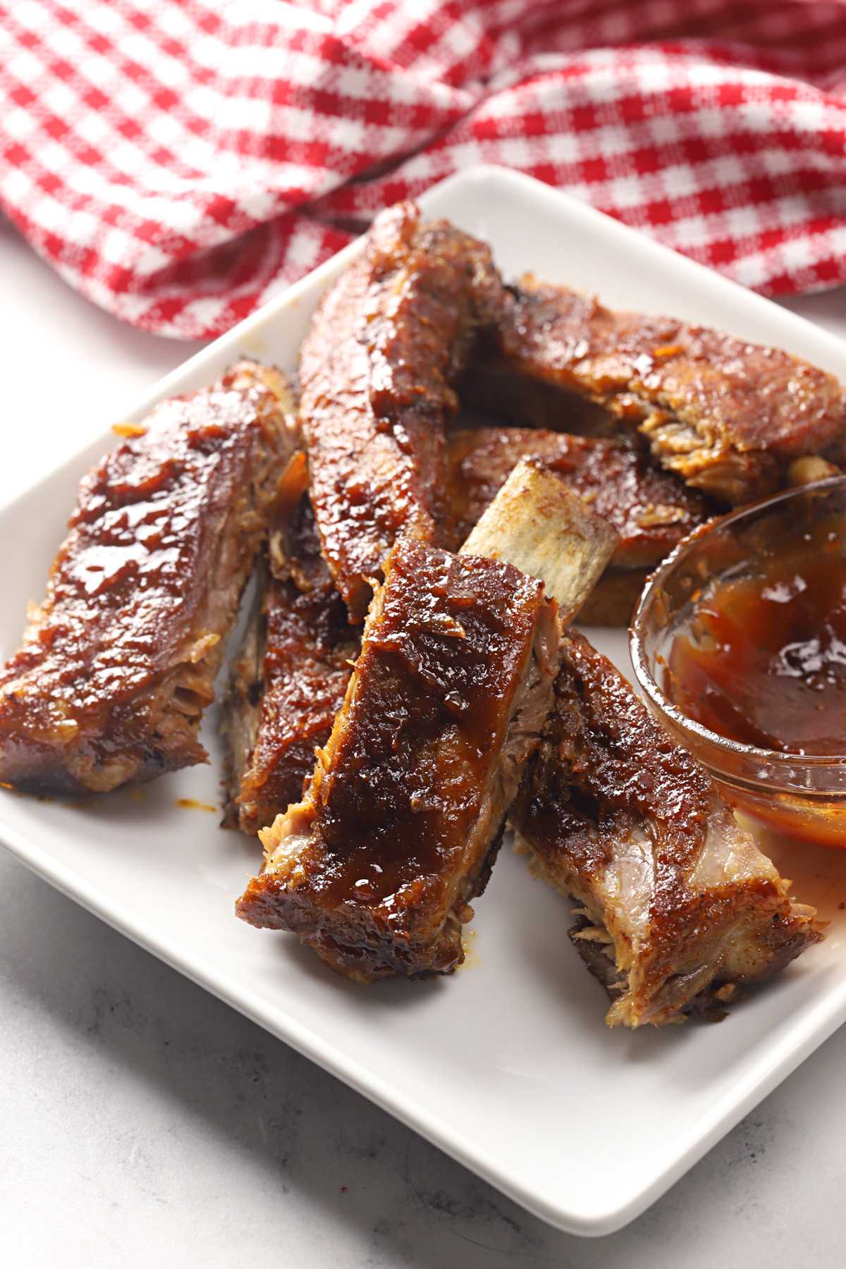 Oven baked ribs on a white plate.