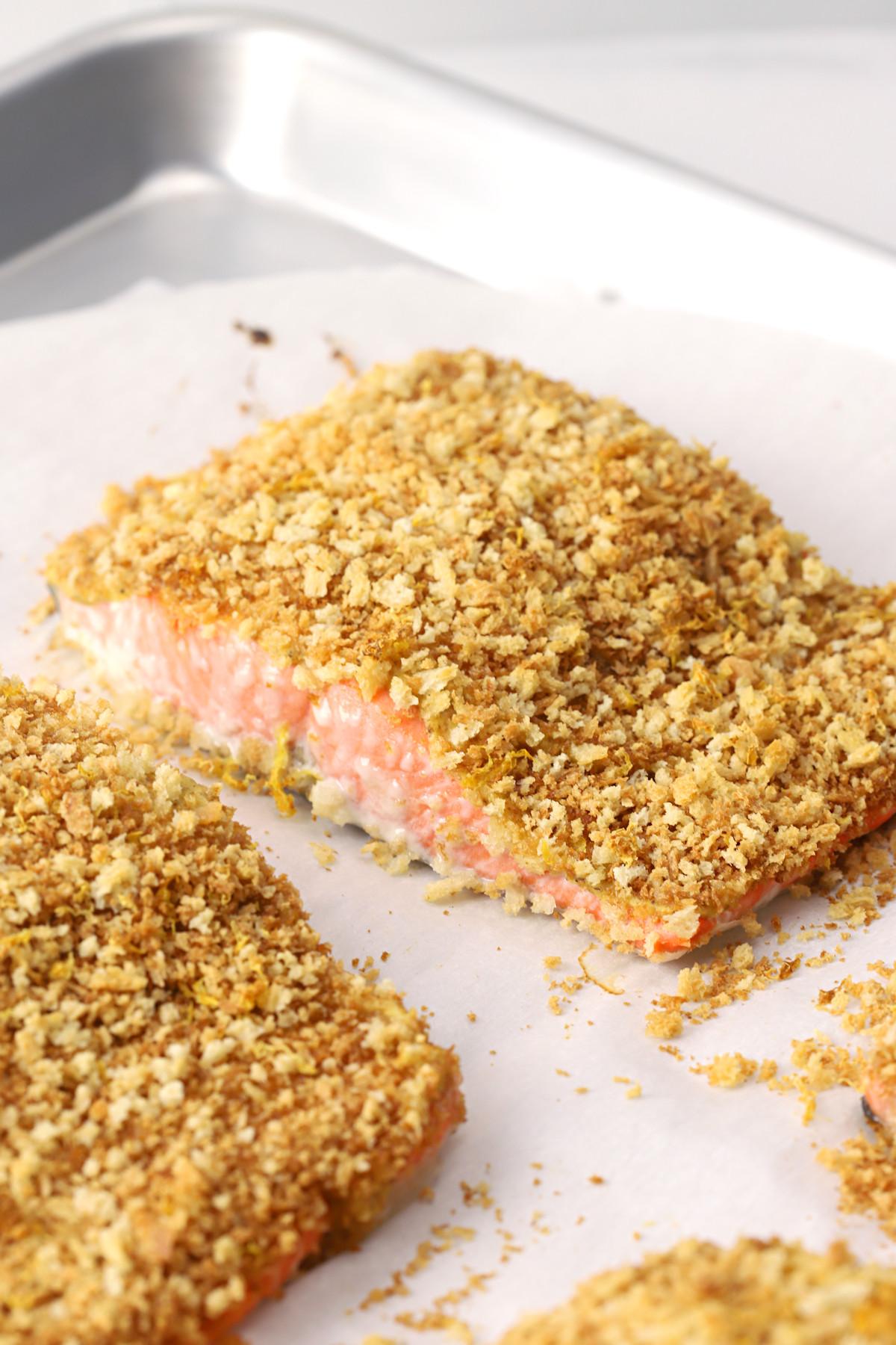 Pieces of panko crusted salmon on a metal sheet pan.