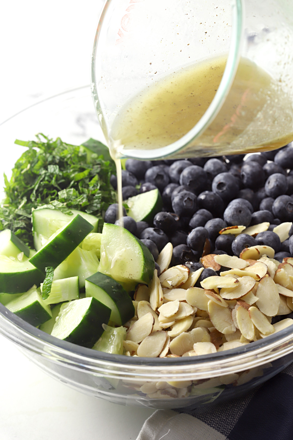 Pouring salad dressing over salad ingredients in a bowl.