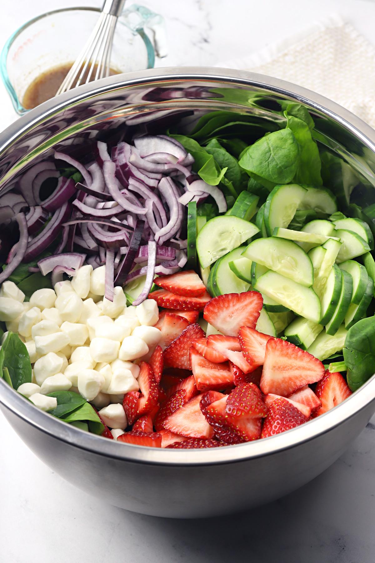 Salad ingredients in a large metal bowl.