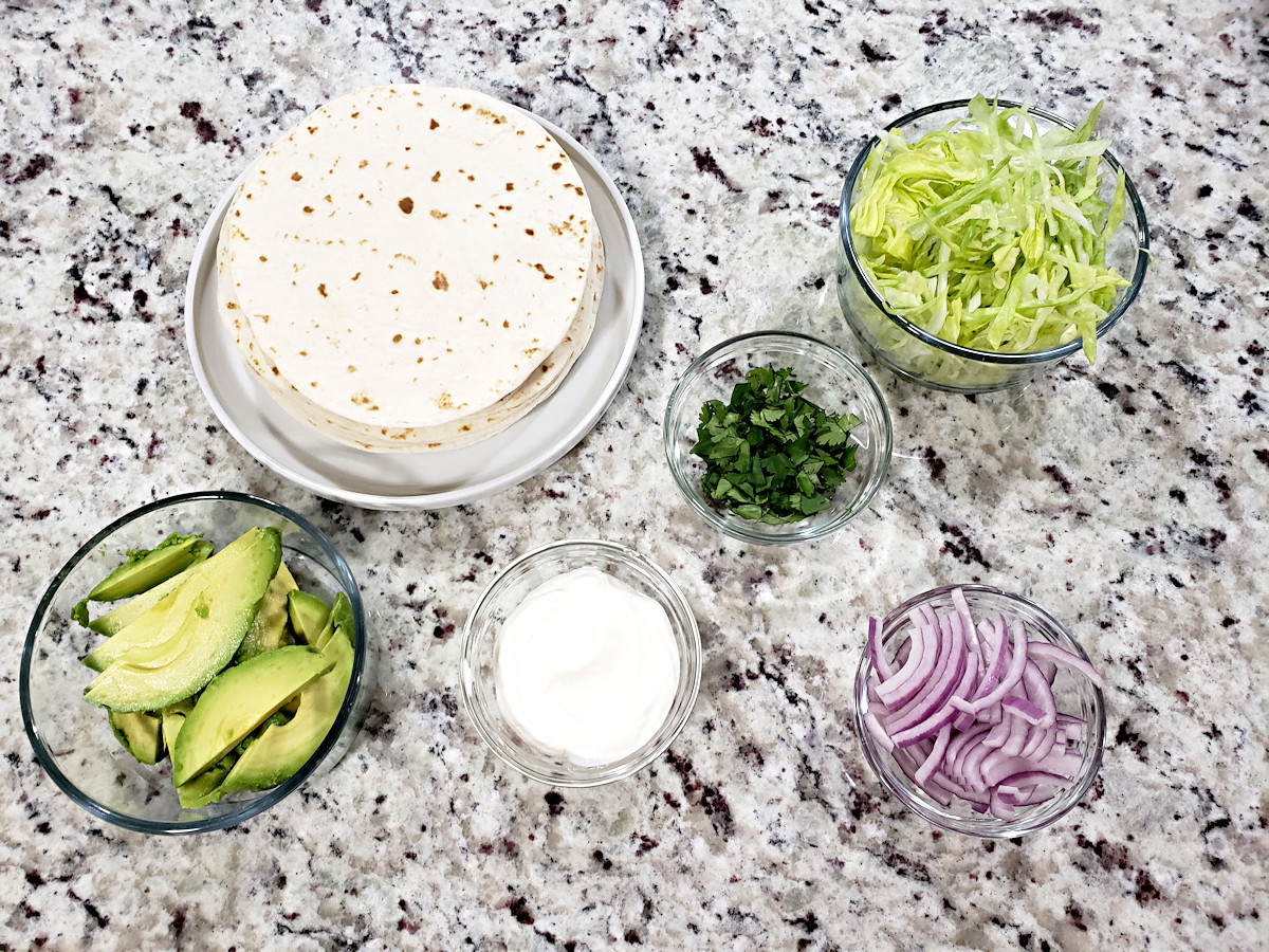Toppings for tacos in a counter top.