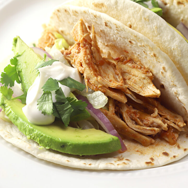 Flour tortilla filled with shredded chicken and taco toppings.