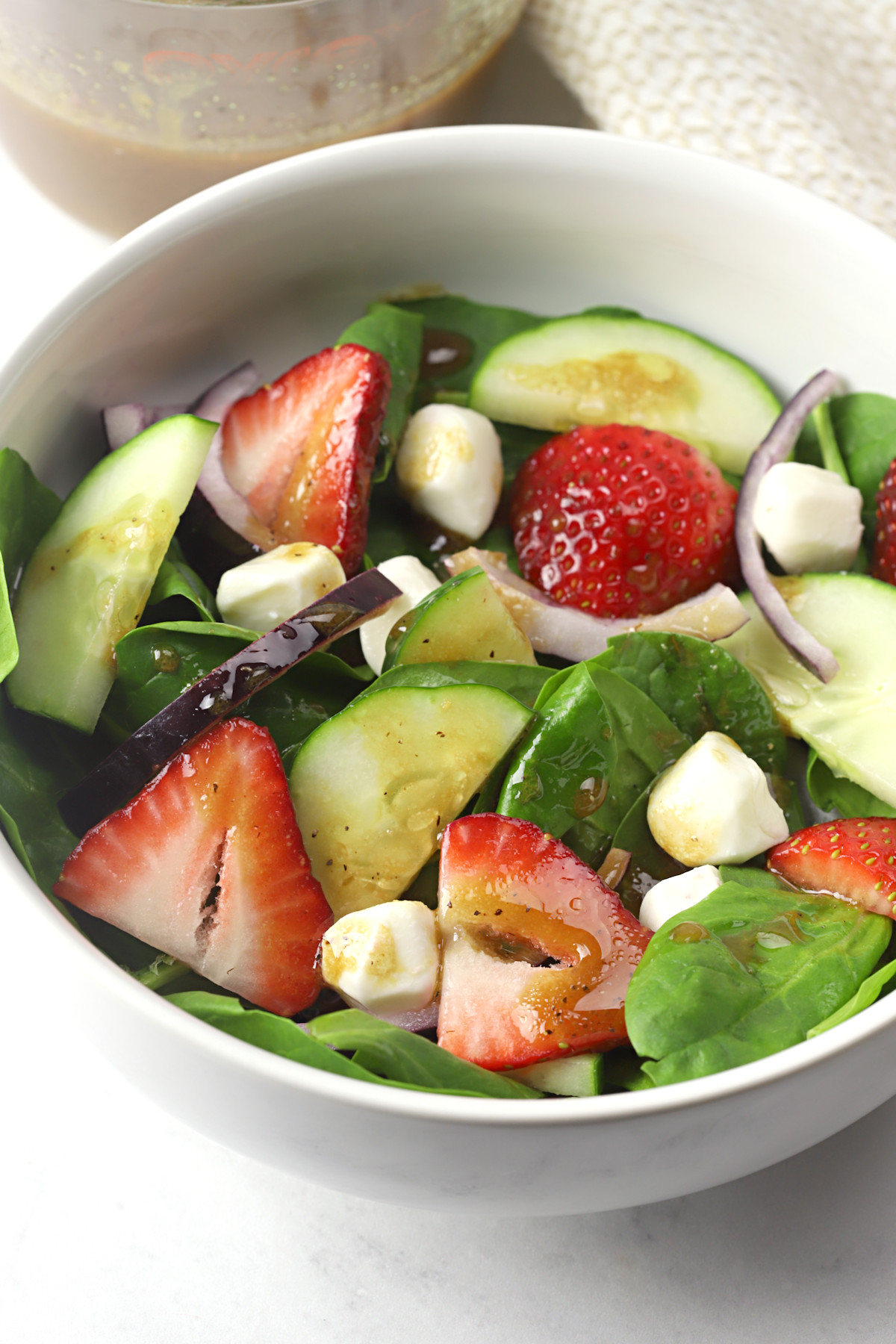 White bowl filled with spinach, strawberries, and cucumbers.