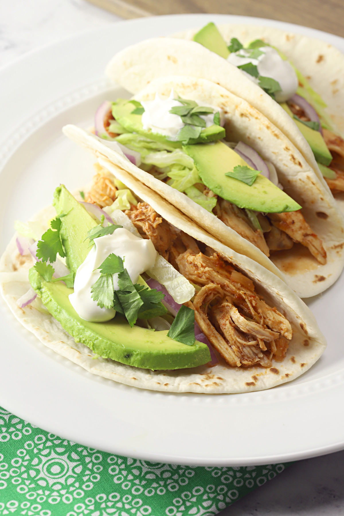 Three chicken tacos on a white plate.