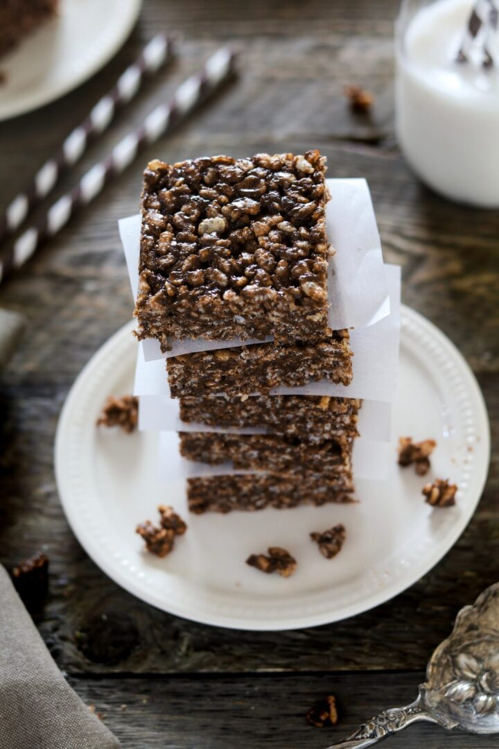 A stack of chocolate dessert bars on a white plate.