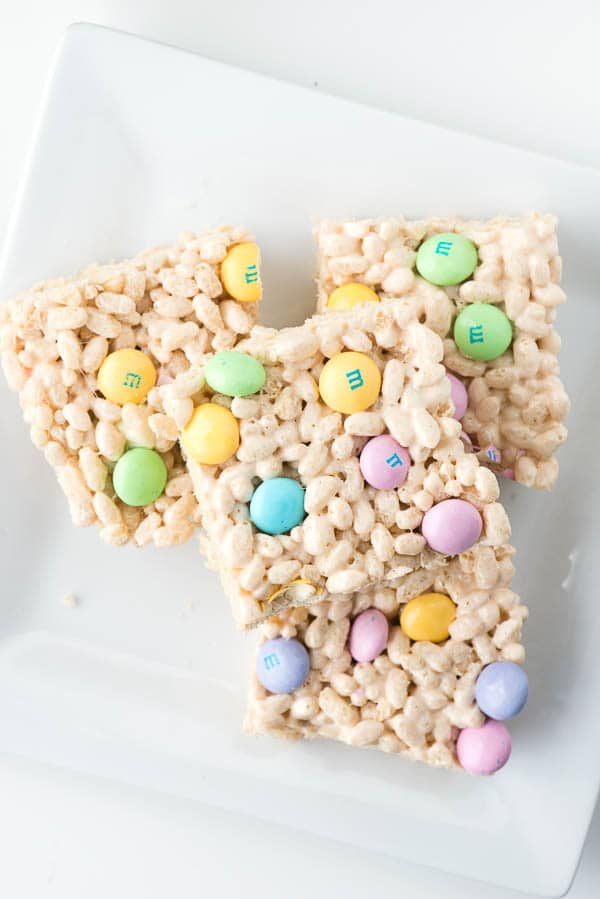 Crispy rice cereal treats decorated with pastel m&m's candies on a piece of parchment.