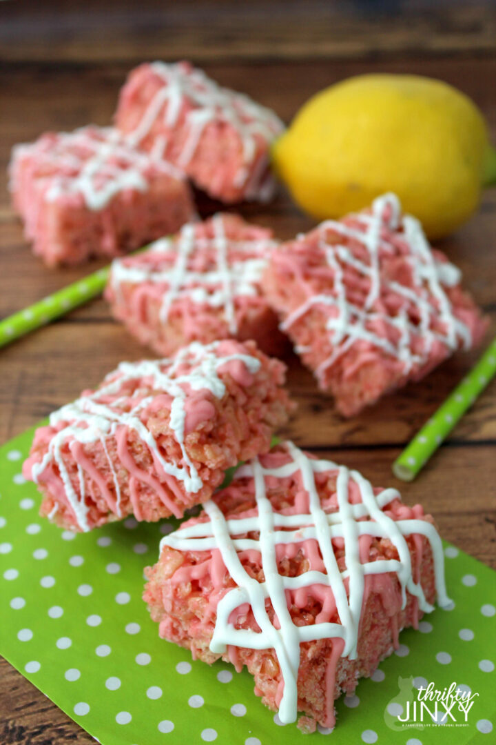 Pink rice krispies treats drizzled in white chocolate.