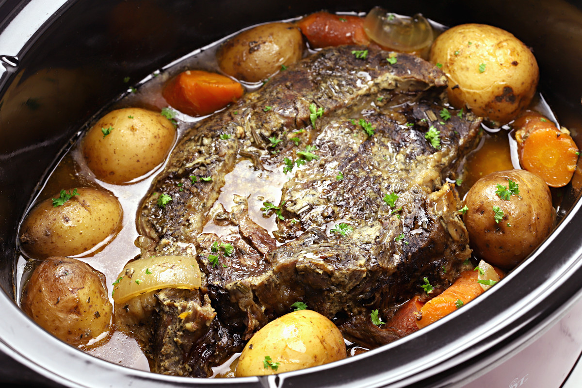 A cooked beef roast surrounded by potatoes and carrots.