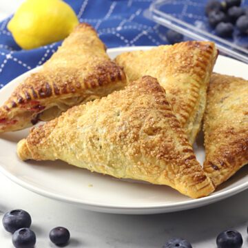 A white plate filled with blueberry turnovers.