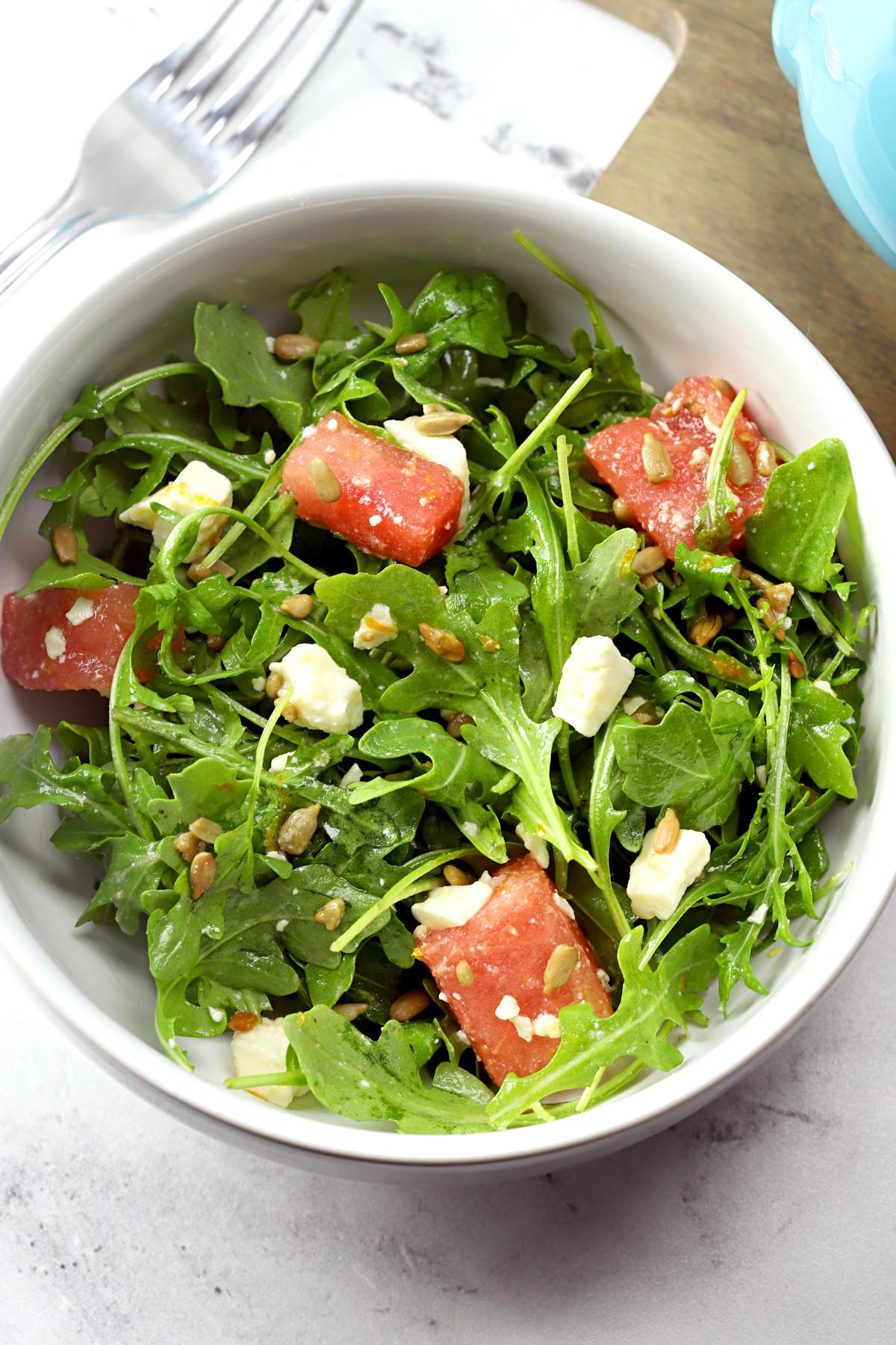 Bowl of arugula salad with watermelon.