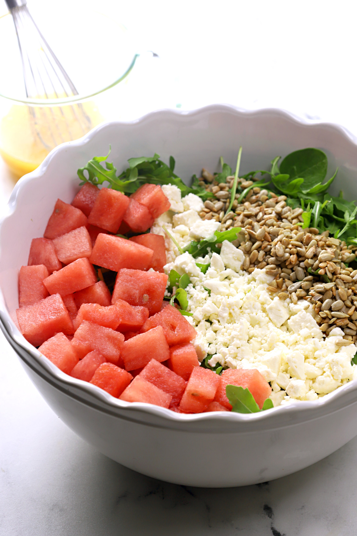 White bowl filled with watermelon, feta cheese, and sunflower seeds.