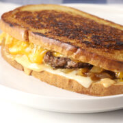 Cheese melting down the side of a patty melt sandwich.