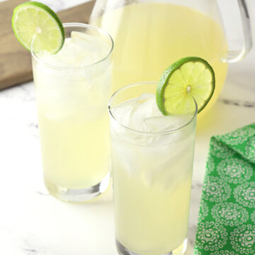 Two glasses of limeade next to a glass pitcher.