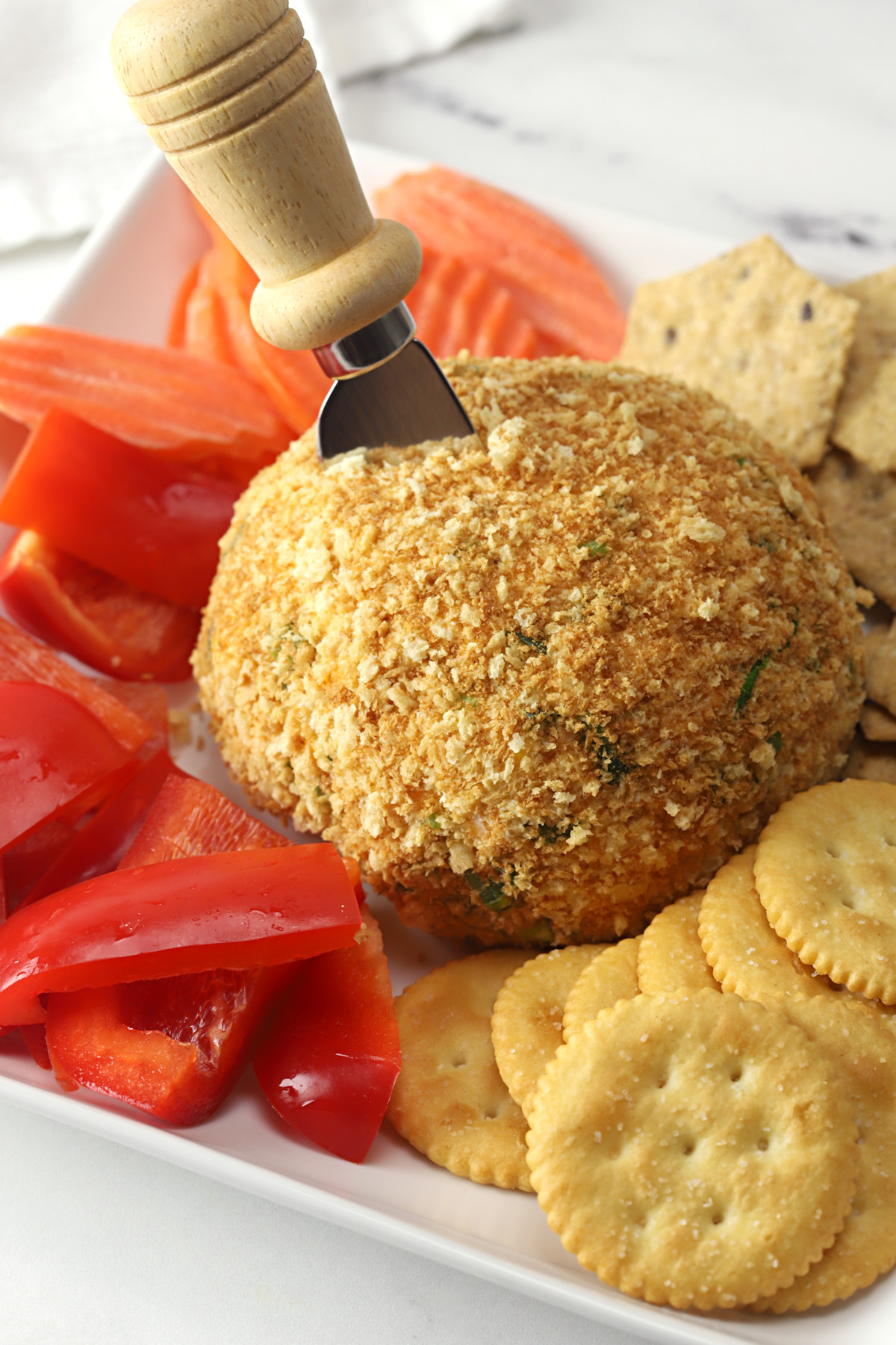 Jalapeño cheese ball with crackers and veggies on a serving plate.