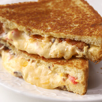 Melty pimento cheese sandwich sliced in half on a plate.