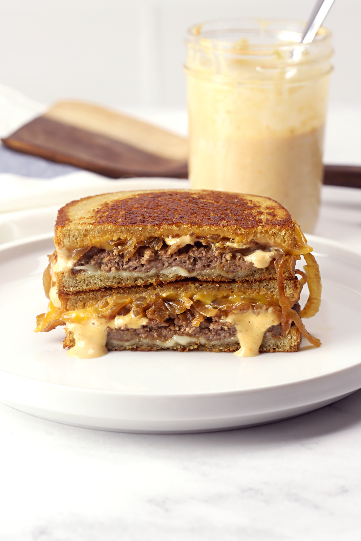 Patty melt sliced in half on a white plate.