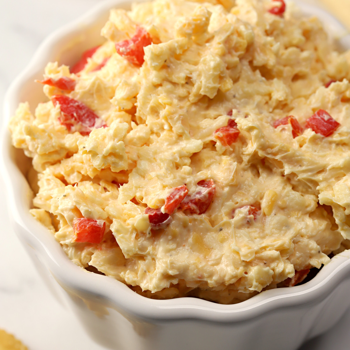 Scalloped bowl filled with pimento cheese.