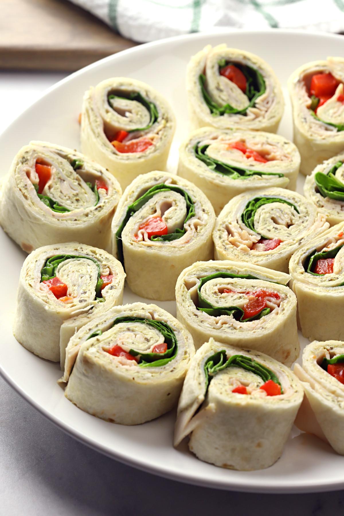 A white plate filled with turkey pesto pinwheel sandwiches.