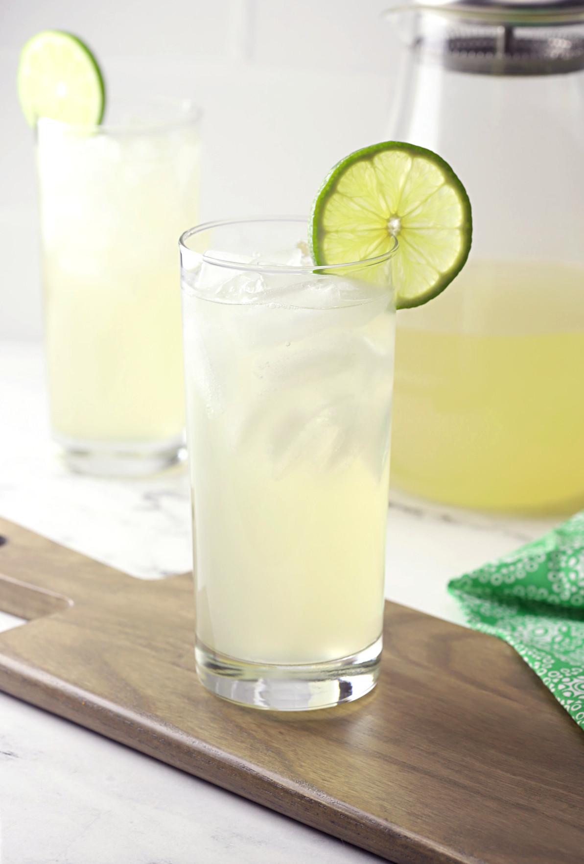 Glass of honey limeade on a wood cutting board.