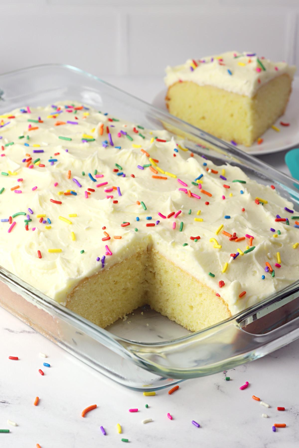 Vanilla sheet cake in a glass pan.