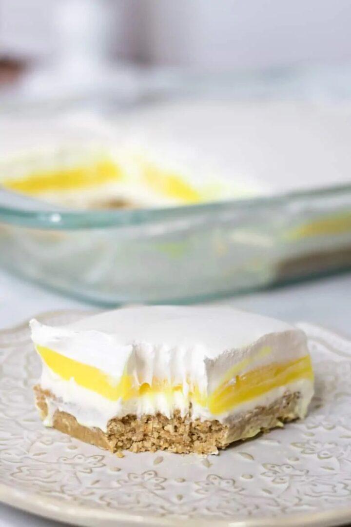 Slice of lemon lush dessert on a white plate.